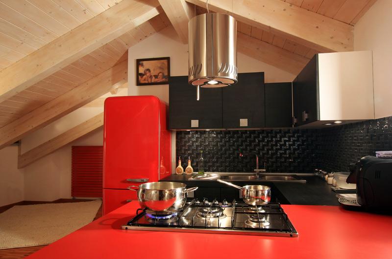 Una piccola cucina angolare in un accogliente mansarda bicromia